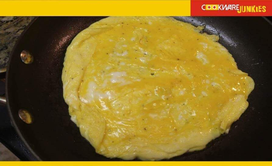 Pic American omelet rolling edges in black pan