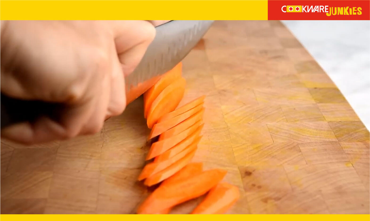 A man making Diagonal cuts of carrot on wood surface