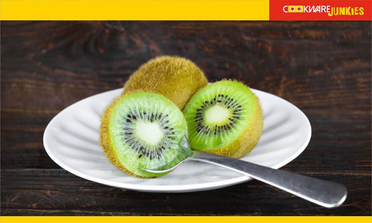 Peeling Kiwi in white plate with spoon