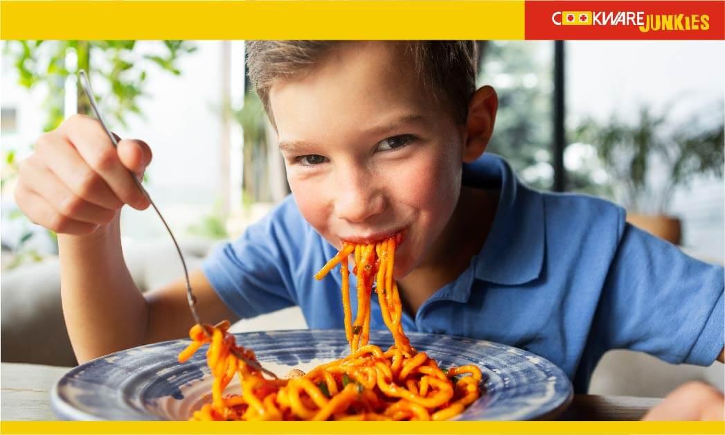 A little boy eating spaghetti