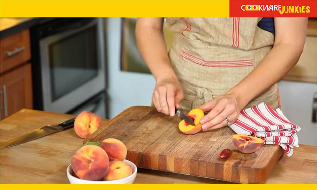 A girl peeling the Peaches on wood surface
