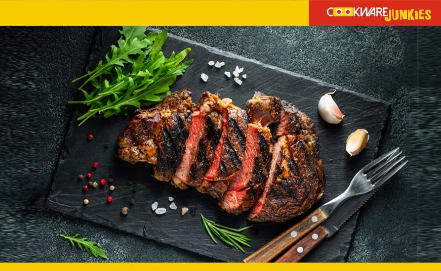 Grilled steak on dark surface with knife and fork