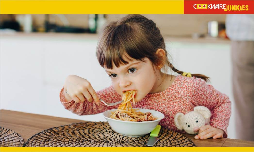 A little girl eating veggies mix with sauce
