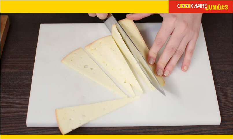 A girl cutting cheese with knife on white surface
