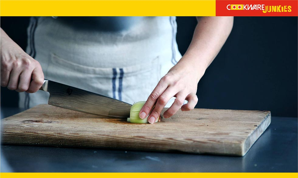 A chef cutting vegetable on wood surface