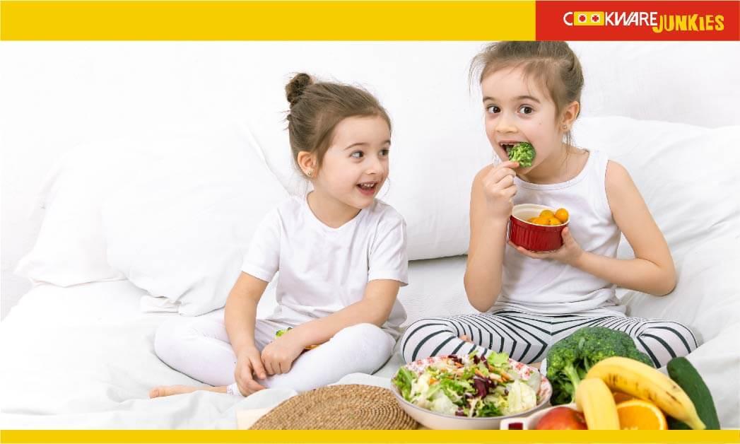 Two little girls eating vegetables
