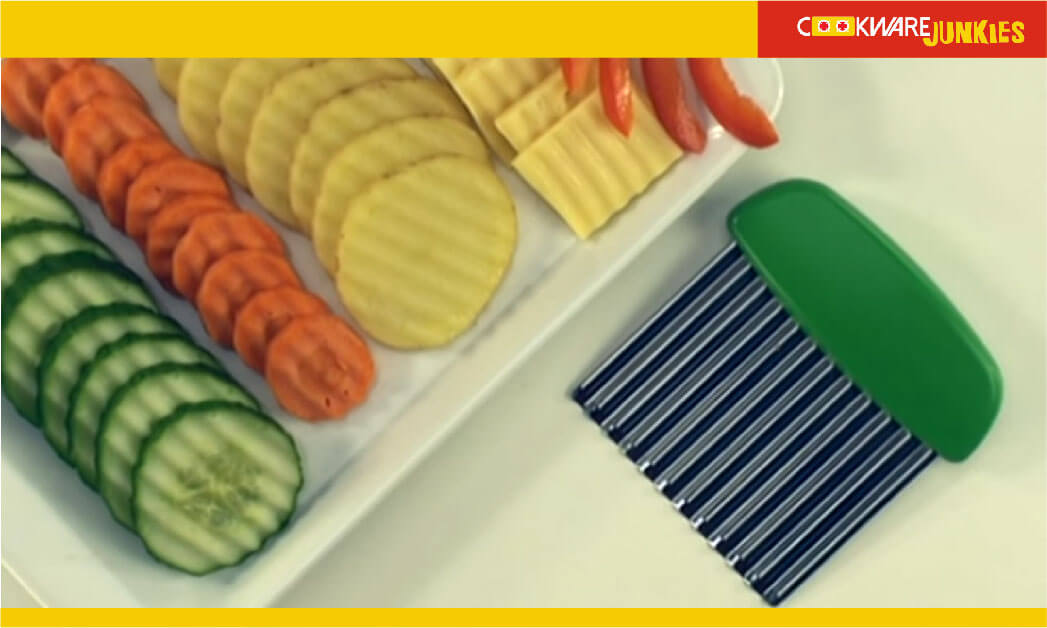 Crinkle cutter with vegetables on white surface